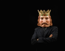 Businessman with king mask and crossed arms